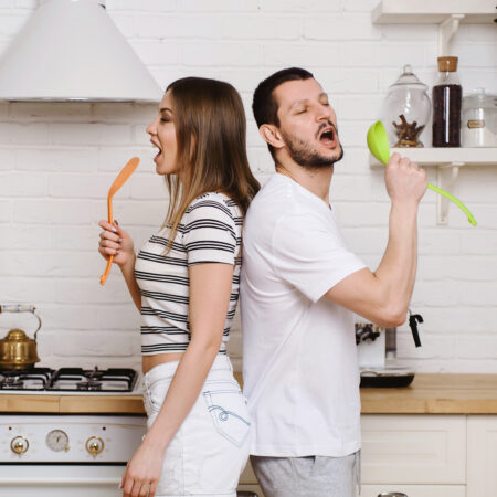 Funny young couple dancing and singing music together enjoying cooking in the kitchen, man and woman in love having fun preparing breakfast food feeling happy and carefree on weekend lifestyle at home